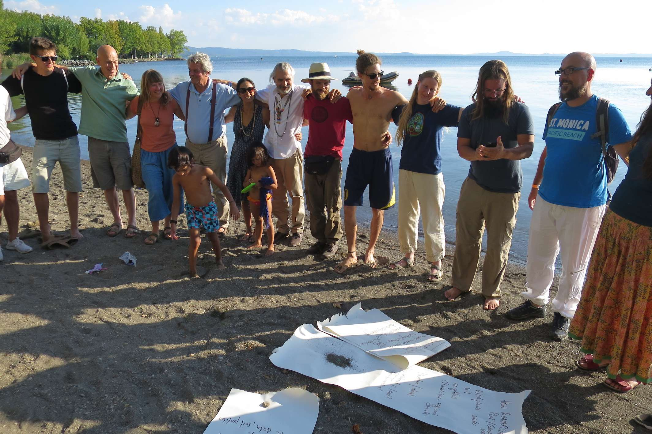 Creating a seed - a circle of people on the beach at the European Permaculture Convergence, held at the beuatiful Bolsena, Italy
