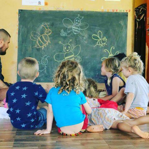Children around a blackboard with bees on it in chalk
